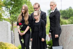 Family on cemetery mourning deceased relative